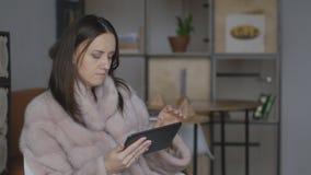 Kvinnasammanträde i ett kafé och surfar internet i sökande av shopping arkivfilmer