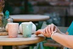 Kvinnasammanträde i ett kafé och vänta på någon som ser till hennes w arkivfoto