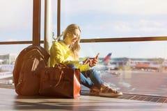 Kvinnasammanträde i flygplats och använda hennes smartphone royaltyfri bild