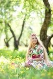 Kvinnasammanträde i gräset royaltyfria bilder
