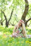 Kvinnasammanträde i gräset fotografering för bildbyråer