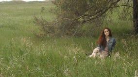 Kvinnasammanträde i grönt fält stock video