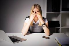 Kvinnasammanträde i hennes kontor med henne täckte ögon royaltyfri fotografi
