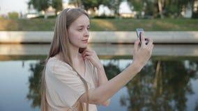 Kvinnasammanträde i parkera och gör selfie som är lycklig På floden lager videofilmer