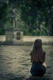 Kvinnasammanträde i regna, med den lite svart klänningen Royaltyfria Bilder