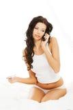 Kvinnasammanträde i säng som stannar till telefonen Royaltyfri Foto