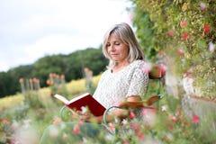 Kvinnasammanträde i stol av trädgården med boken i händer Arkivbild