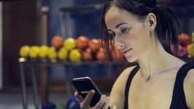 Kvinnasammanträde inom idrottshall och att se i telefonen som kopplar av stock video