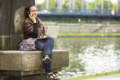 Kvinnasammanträde med bärbara datorn utomhus, i staden och samtal på telefonen Royaltyfria Foton