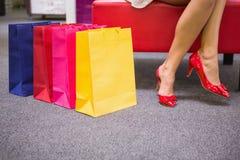 Kvinnasammanträde med ben korsade bredvid shoppingpåsar Arkivfoto