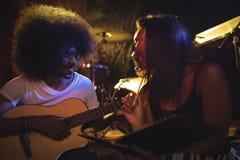 Kvinnasammanträde med den manliga gitarristen som öva i nattklubb arkivbild