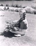 Kvinnasammanträde med korgen av blommor Royaltyfri Foto