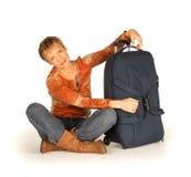 Kvinnasammanträde med resväskan på vit Arkivfoton