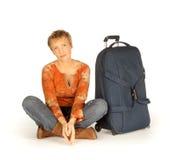 Kvinnasammanträde med resväskan på vit Arkivbild