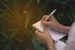 Kvinnasammanträde och innehav en blått blyertspenna och göra Arkivbilder