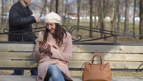 Kvinnasammanträde på bänk med telefonen och rånaren med hennes handväska lager videofilmer