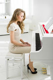 Kvinnasammanträde på bänk och se pianot arkivbilder