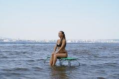 Kvinnasammanträde på bänken i federationen för flodvolga ryss Arkivfoto