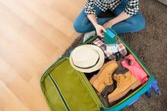 Kvinnasammanträde på bagage för vardagsrumgolvemballage arkivbilder