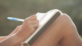Kvinnasammanträde på balkongen och handstil i dagbok med trädgården på bakgrunden lager videofilmer