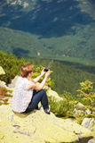 Kvinnasammanträde på berget Royaltyfri Foto