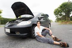 Kvinnasammanträde på bygdvägen med den brutna bilen royaltyfri foto
