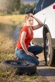 Kvinnasammanträde på den brutna bilen och försöka att ändra det plana gummihjulet Fotografering för Bildbyråer