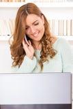Kvinnasammanträde på den hemmastadda soffan och användabärbara datorn och att tala på mobil royaltyfri bild