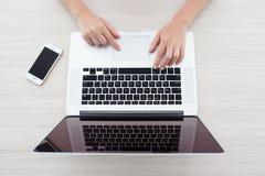 Kvinnasammanträde på den MacBook Pro näthinnan och iPhonen 5s Arkivfoton