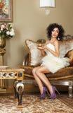 Kvinnasammanträde på den Retro soffan med locket av kaffe. Klassisk inre Royaltyfri Foto