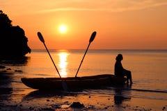 Kvinnasammanträde på en kajak på stranden Arkivfoto