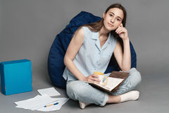 Kvinnasammanträde på en kuddepåse och innehav en anteckningsbok i händer Isolerat på grå bakgrund Arkivfoton