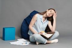 Kvinnasammanträde på en kuddepåse och innehav en anteckningsbok i händer på grå bakgrund Fotografering för Bildbyråer