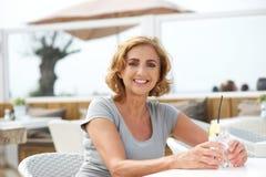 Kvinnasammanträde på en restaurang som kopplar av med exponeringsglas av vatten Royaltyfri Bild