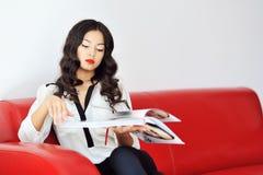 Kvinnasammanträde på en soffa och en läs- tidskrift royaltyfri bild