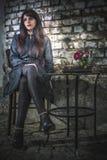 Kvinnasammanträde på en stol i coffee shop royaltyfri bild