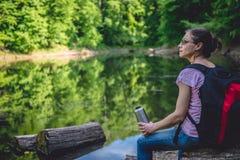 Kvinnasammanträde på en trädjournal vid sjön fotografering för bildbyråer