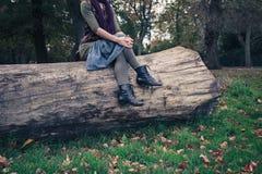 Kvinnasammanträde på ett stupat träd i parkera Royaltyfri Foto