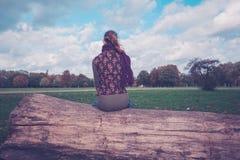Kvinnasammanträde på ett stupat träd i parkera Royaltyfria Bilder