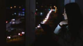 Kvinnasammanträde på fönsterbrädan i den mörka natten och att se gatan Läsebok i minnestavla stock video