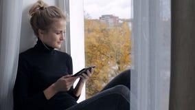 Kvinnasammanträde på fönsterbrädan och läser en bok i e-avläsare lager videofilmer