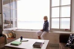 Kvinnasammanträde på fönstret och se härlig strandsikt Royaltyfria Bilder