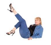 Kvinnasammanträde på golv med ben upp Arkivfoto