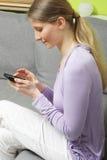 Kvinnasammanträde på golvet med hennes telefon Fotografering för Bildbyråer