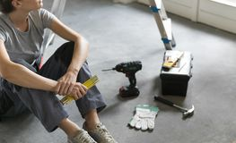 Kvinnasammanträde på golvet och planläggningen en hem- renovering arkivbild