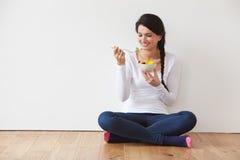 Kvinnasammanträde på golvet som äter bunken av ny frukt arkivbilder