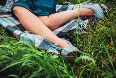 Kvinnasammanträde på gräset Royaltyfria Bilder