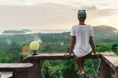 Kvinnasammanträde på höjdpunkten som förbiser ön på soluppgång arkivfoto
