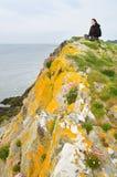 Kvinnasammanträde på havsklippor Royaltyfri Bild