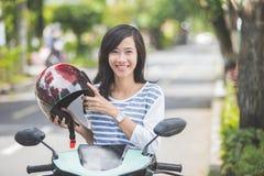 Kvinnasammanträde på hennes moped royaltyfri fotografi